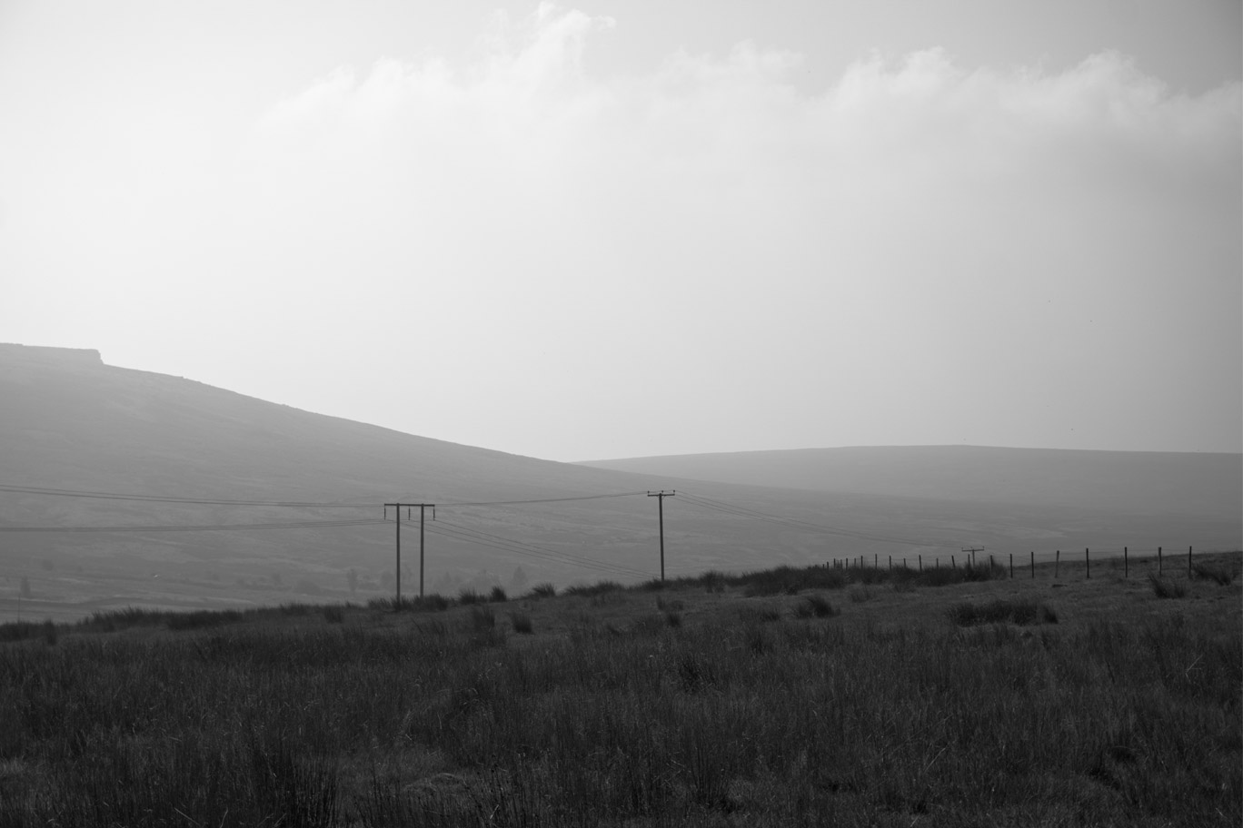 Black and white image of pylons through the countryside